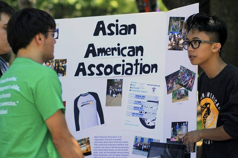 Asian American Association representative talking to students at a recruitment booth